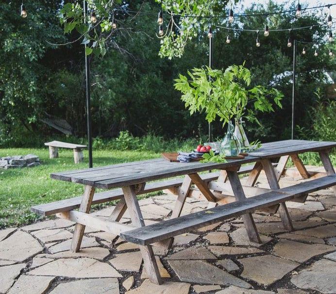 schöner sitzplatz im garten mit steinboden und diy holzesstisch mit sitzbänken