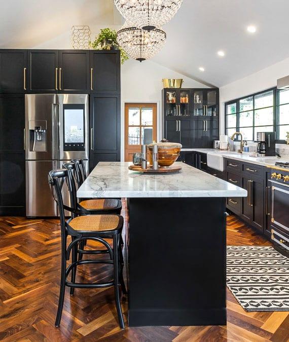 attraktive küchengestaltung in schwarz und messing kombination mit parkettboden in fischgrätmuster,kristall kronleuchtern über esstheke aus marmor und smart sidy by side kühlschrank samsumg