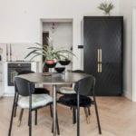 küche mit hellem parkettboden attraktiv und raffiniert einrichten mit weißen Küchenschränken, freistehendem side by side kühlschrank schwarz und rundem esstisch mit schwarzen holzstühlen,