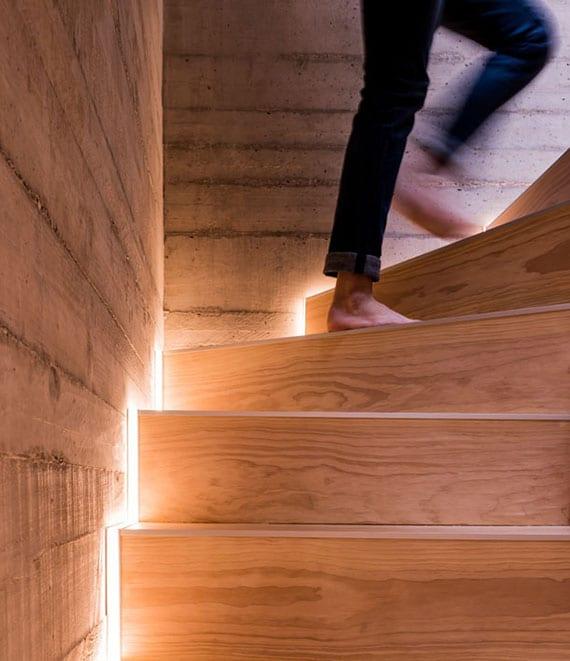 treppenhaus gestalten mit sichtbetonwänden und holztreppe mit automatischer LED treppenbeleuchtung