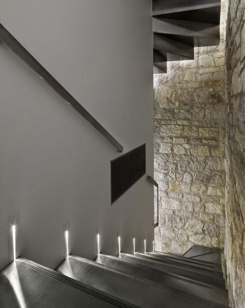 treppenhaus mit auskragender stahlblechtreppe und steinmauer modern gestalten und beleuchtenmit