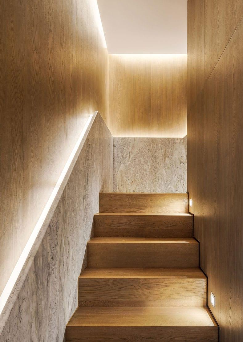 treppenhaus modern gestalten mit wandverkleidung aus holz und naturstein und effektvoll ausleuchten durch LED-Handlaufbeleuchtung