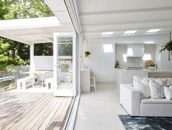 eine große Terrasse mit holzboden und glasbalustrada erweitert im Sommer das offene Wohnzimmer nach draußen