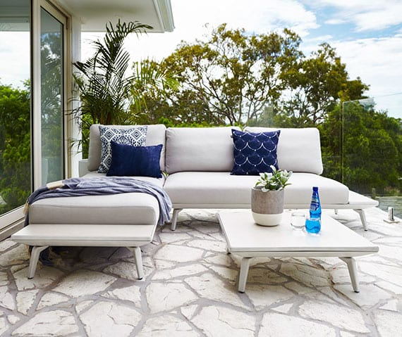 mediterrane terrassengestaltung mit bodenbelag aus steinen und moderner ecksofa mit kaffeetisch aus metall