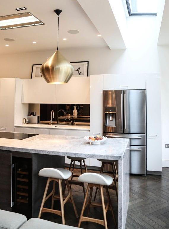 stilvolle wohnküche in weiß mit spiegelrückwand, sidy-by-side kühlschrank mit wasserspender, kochinsel in marmor optik mit kochfeld, kühlfach für flaschen und esstheke für vier personen