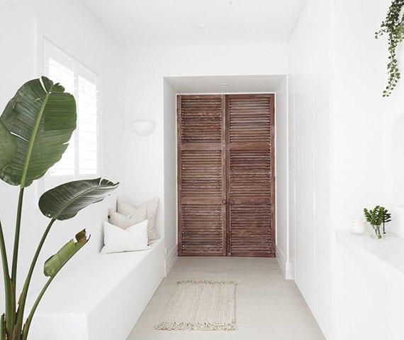 coole idee für attraktive raumgestaltung vom windfang mit Fensterladen-Türflügeln und ausgemauerter sitzbank mit kissen unter fenster mit weißen Jalousien