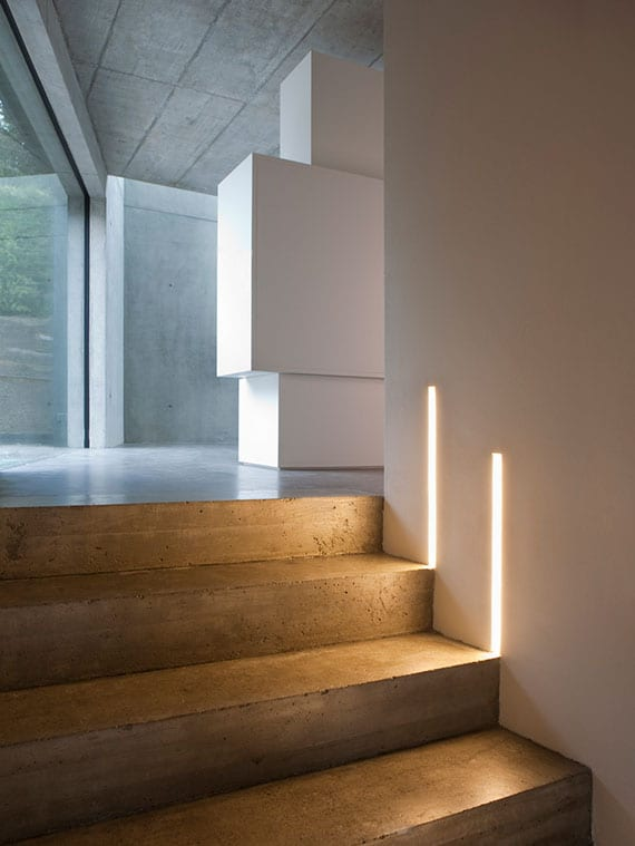 minimalistischen treppenbereich mit betontreppe und weißen wänden attraktiv beleuchten mit vertikal montierten LED-Wandeinbauleuchten