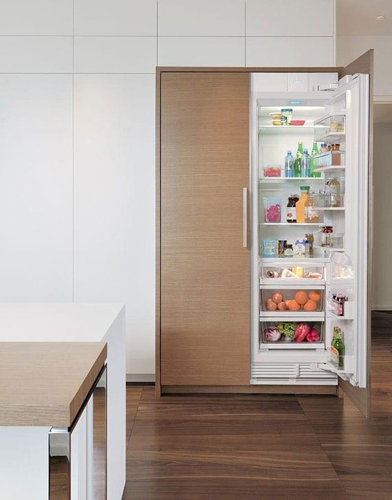 stilvolle küchengestaltung mit holzbodenbelag, einbauküche weiß, einbaukühlschrank in holzoptik und kochinsel mit esstheke aus holz