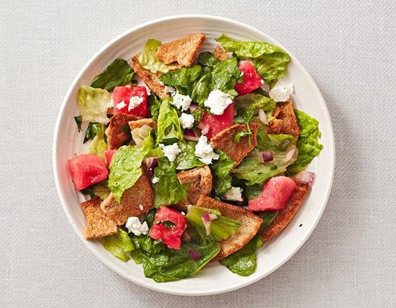 Melonensalat mit Feta, Tomaten, Salatblättern, Zwiebel und Fladenbrot