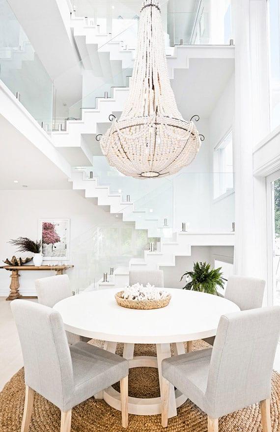schickes interioer design im dreigeschossigen haus mit empore und großem perlen-kronleuchter über rundem esstisch aus holz für sechs personen