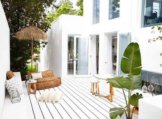 mediteranne-terrassengestaltung-in-weiß-als-attraktive-gartenecke-mit-sitzbank,-sichtschutzmauer,bodenkissen-aus-jute-und-sonnenschirm