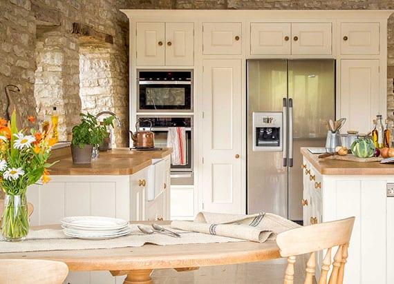 attraktive küche in mediterranem stil mit klassischen küchenschränken in weiß und holz, rundem holzesstisch und side by side kühlschrank mit wasserspender
