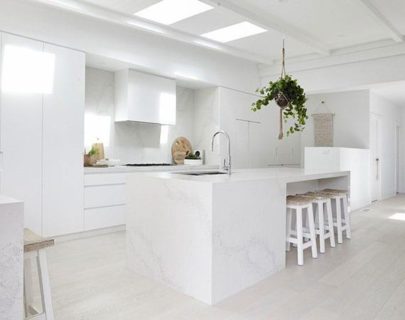 raffinierte gestaltungsidee für moderne wohnküche mit ess-und kochinsel in marmor optik, hellem parkettboden und einbaukühlschrank in weiß