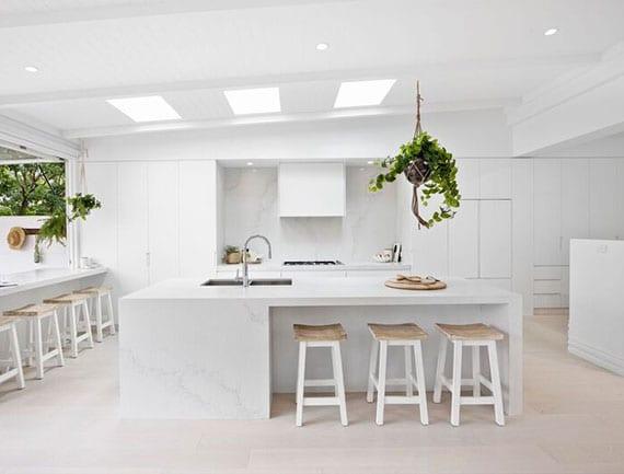weiße wohnküche mit esstheke vor Klapp-Schwingfenster, kücheninsel mit sitzmöglichkeit und hängepflanzen als akzent zu weißem interieur