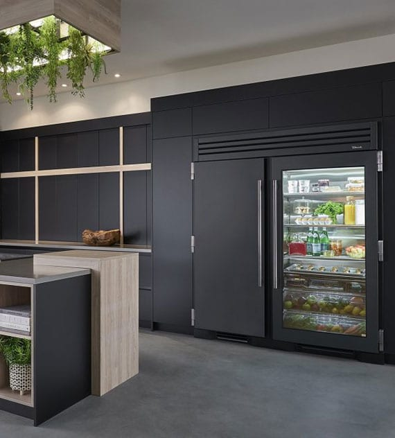 moderne einbauküche schwarz mit Side-by-Side kühlschrank als einbaugerät mit glastür und atraktiver deckenlampe mit begrünung über kochinsel