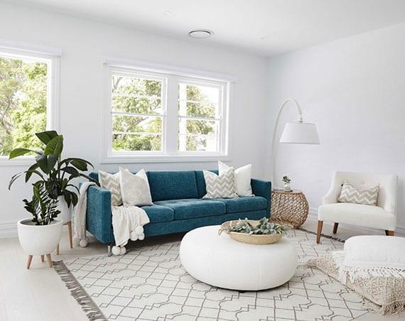 kleines wohnzimmer stilvoll einrichten mit 3er sofa in blau, rundem hocker-tisch weiß und bodenkissen auf gemustertem teppich, ratan beistelltisch und modernen Pflanzkübel weiß