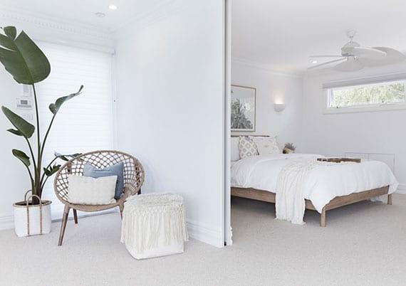 schlafzimmer schlicht und modern in weiß einrichten mit holzbett, flechtsessel und pflanze in weidenkorb