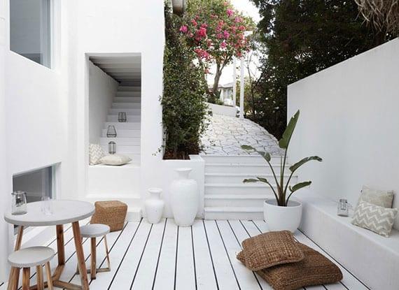 mediterrane terrasse in weiß mit sichtschutzwand und ausgemauerter gartenbank, rundem kaffeetisch mit runden hockern, alte treppe als sitzgelegenheit mit windlichtern und weißen vasen