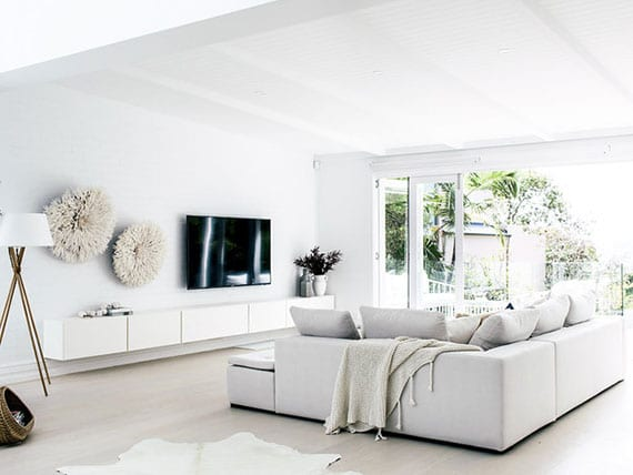 stilvolle wohzimmereinrichtung mit designer-ecksofa in weiß, tv lowboard und attraktiver Juju-Hat-Wanddeko