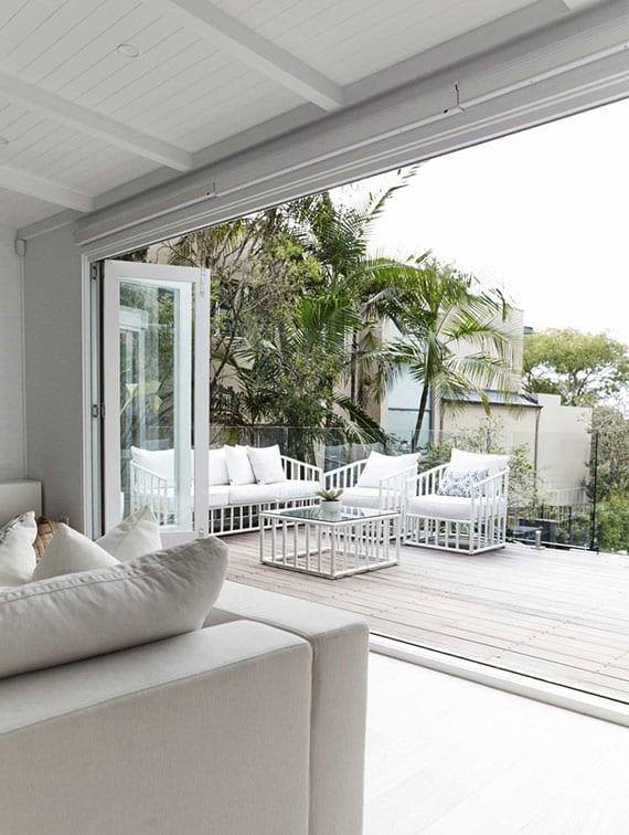 mediterrane terrasse mit holzboden und weißen gartenmöbeln mit wohnzimmer verbinden durch falttür