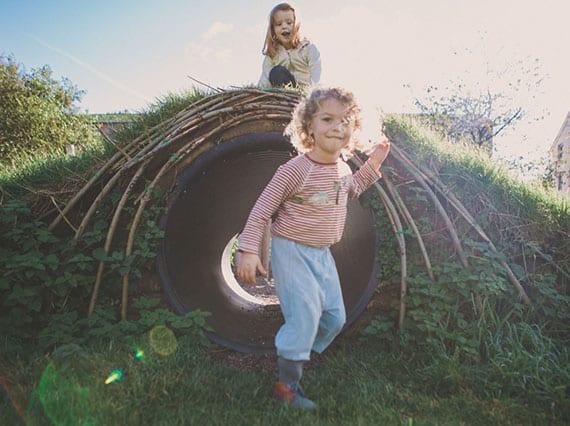begrünter spielhügel mit tunnel als idee für kinderspielplatz im garten