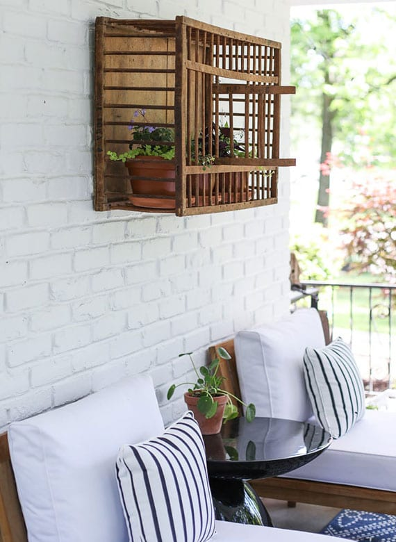 coole terrassengestaltung mit weißer ziegelwand, zwei holzsesseln mit weißen polstern, rundem kaffeetisch schwarz und diy hühnerkiste-wandregal mit blumentöpfen