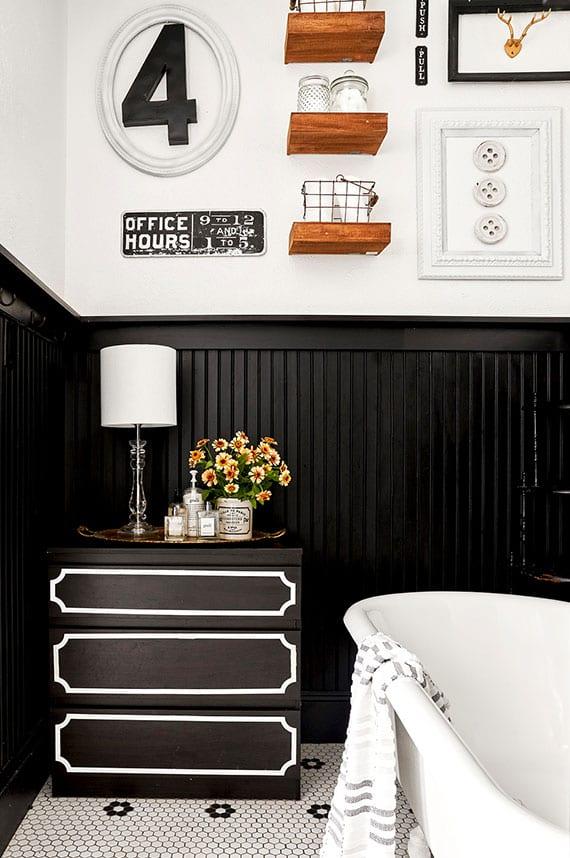 vintage bad design in schwarz und weiß mit kommode als beistelltisch neben der badewanne, holzregalen und rustikale wanddeko mit fundstücken