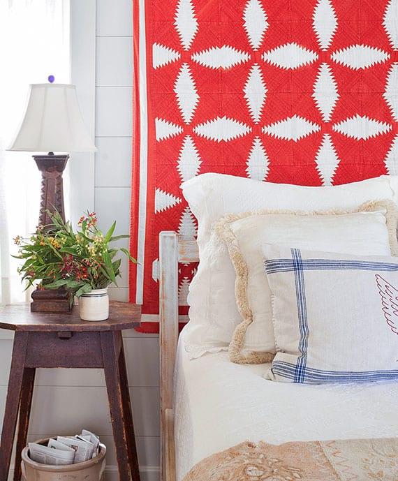 rustikales schlafzimmer interieur mit antikelm holzbeisteltisch, tischlampe aus holz und roter bettdecke als wanddeko