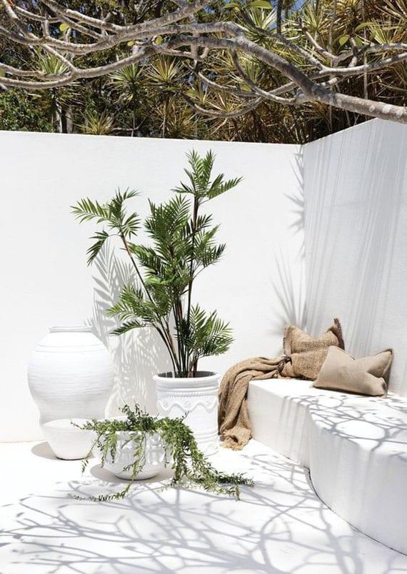 schöne garten sitzecke in weiß mit weißer gartenmauer als sichtschutz, ausgemauerter sitzbank mit kissen und grüne topfpflanzen in weißen blumenkübeln