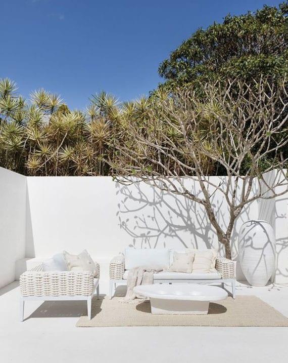 stilvolle terrasse ganz in weiß gestalten mit designer gartenmöbeln aus rattan und diy couchtisch aus beton auf teppich für außenbereich in beige