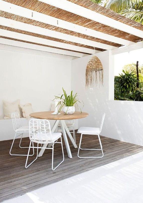 mediterrane Terrasse gestalten in weiß mit einer terrassenüberdachung aus stroh, natürlichem holzboden und rundem esstisch mit weißen gartenstühlen aus metall