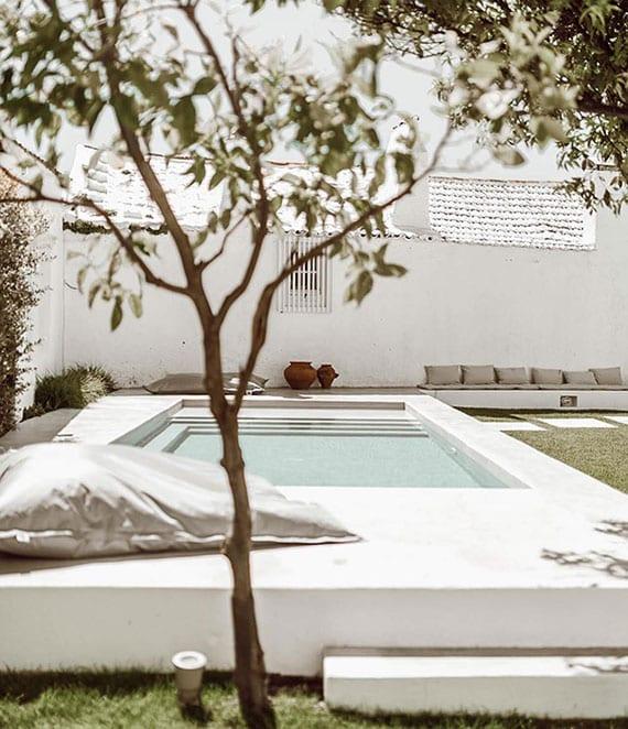 sommeroase im garten gestalten mit gartenpool in weiß und gemauerter sitzbank mit grauen polstern