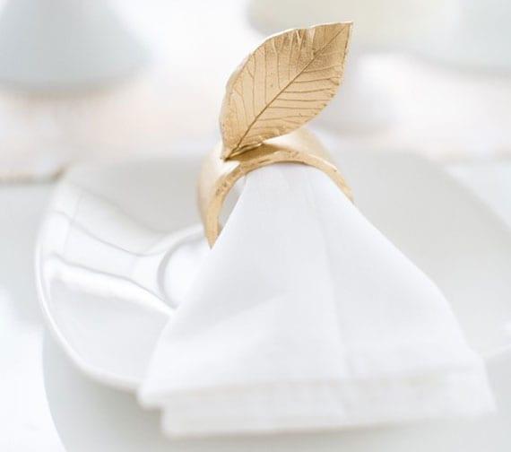 tisch festlich und glamourös decken mit weißen stoffservietten in goldenen serviettenringen mit blatt