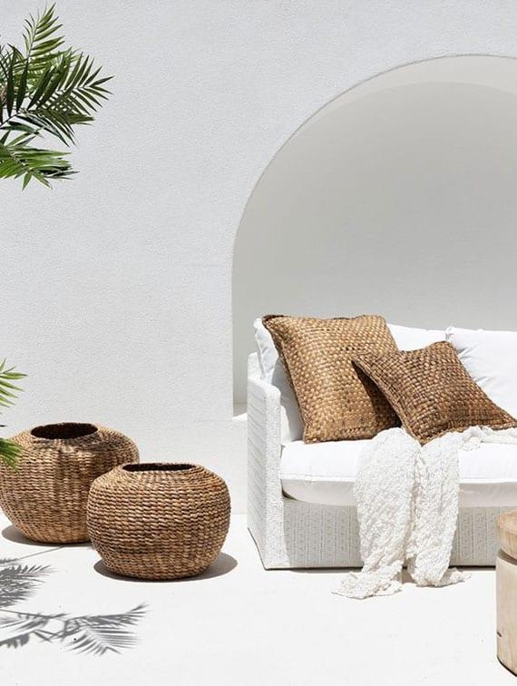 terrasse mediterran gestalten durch die kombination von wandfarbe weiß mit rattanmöbel, weißen schaumstoffkissen und weidenkörben