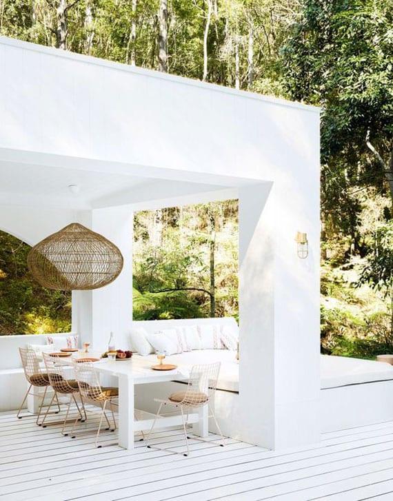 reizvolle terrassenidee in weiß mit stylishem daybed und essplatz mit weißem holztisch und metalldrahtstüheln unter terrassenüberdachung