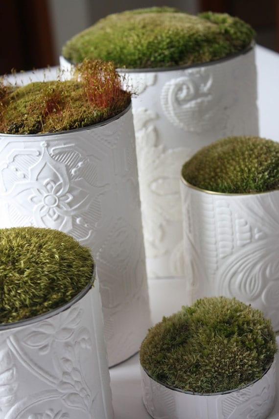 stilvolle und natürliche upcycling deko  mit frischem moos in konservendosen mit einer Tapetenverzierung in weiß