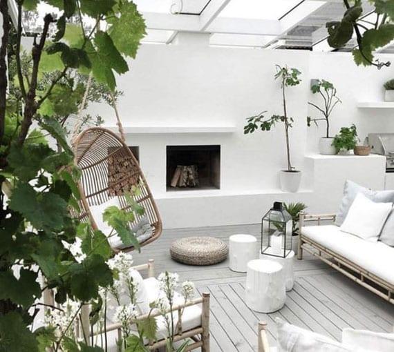 attraktive gestaltungsidee für kleine überdachte terrasse mit holzdiele in grau, gartenmöbel aus bambus, kaminofen in der wand und rattan-schaukelstuhl