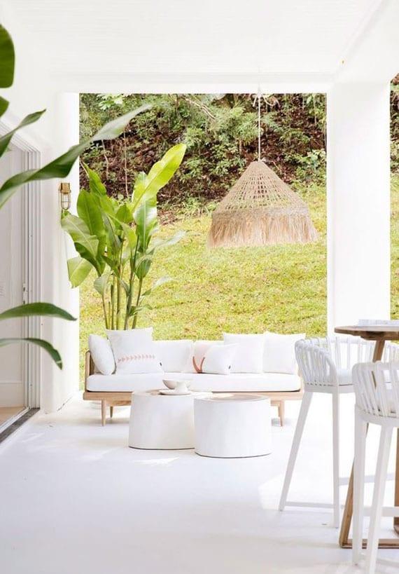 überdachte terrasse im garten ganz im weiß gestalten und mit gartensofa aus holz und diy kaffeetischen aus baumstamm effektvol einrichten