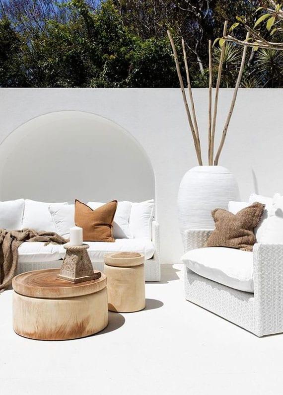 weiße gartenterrasse und moderne sitzecke mit weißen lounge möbeln und runden holztischen