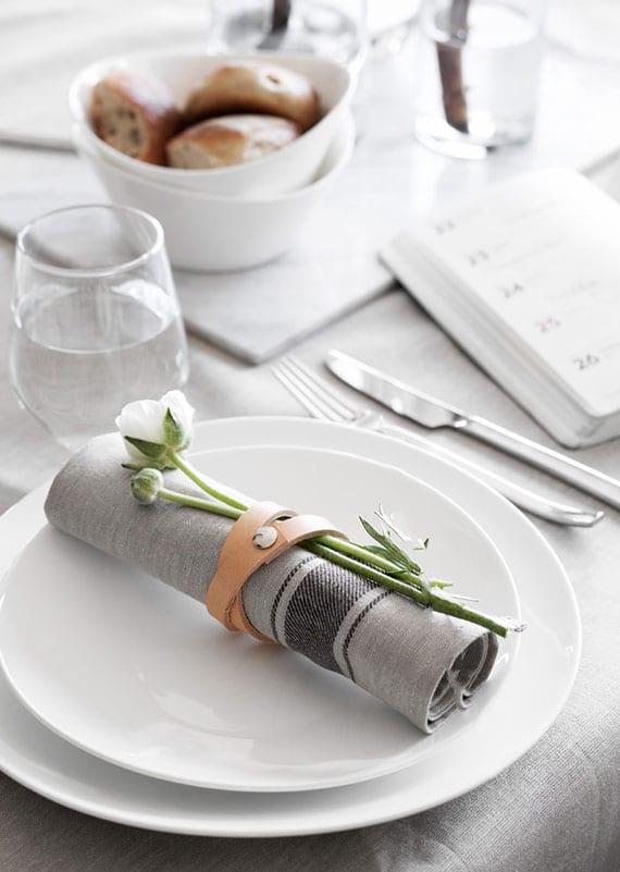 graue stoffserviette mit weißer Blume in diy serviettenring aus lederband falten und als schöne platzteller deko setzen