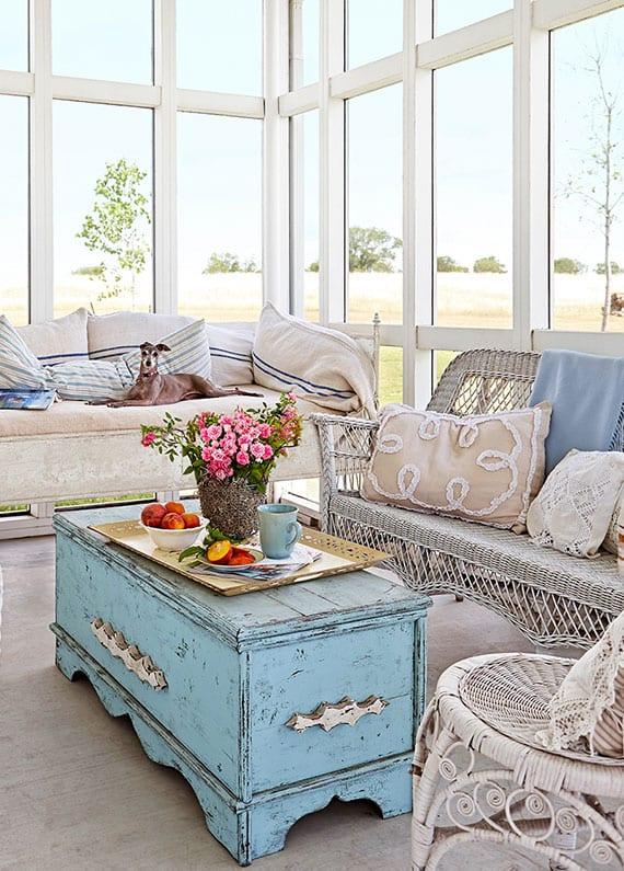 einrichtungsidee für wohnzimmer im shabby chic wohnstil mit weißen rattanmöbeln und diy couchtisch aus aler holztruhe in hellblau
