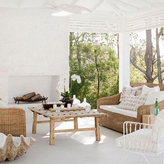 schöne terrassenideen in weiß für gestaltung gemütlicher sitzecke im rustikalen stil mit rattanmöbeln, anikem kaffeetisch holz, kaminofen und holzpergola