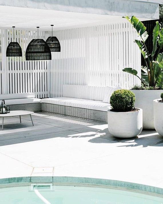gartenterrasse idee in weiß und beton mit holzlatten-sichtschutzwänden, schwarzen weidenlampenschirmen und runden pflanzenkübeln aus beton