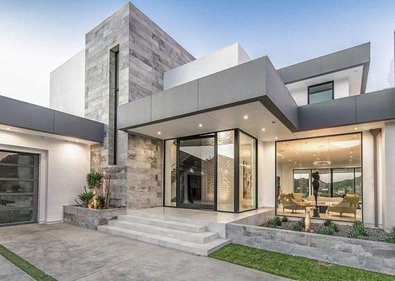 modernes Kubus-Haus in weiß mit Flachdachkonstruktion und Attika in grau, naturstein wandverkleidung und überdachtem hauseingang mit verglasung