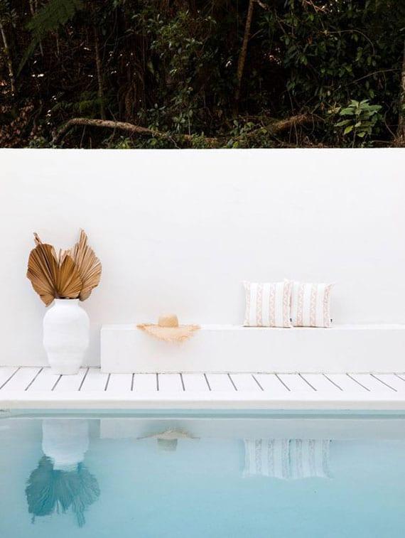 traumhafte idee für sitzecke im garten mit weißen mauern. weißer sitzbank aus beton und pool