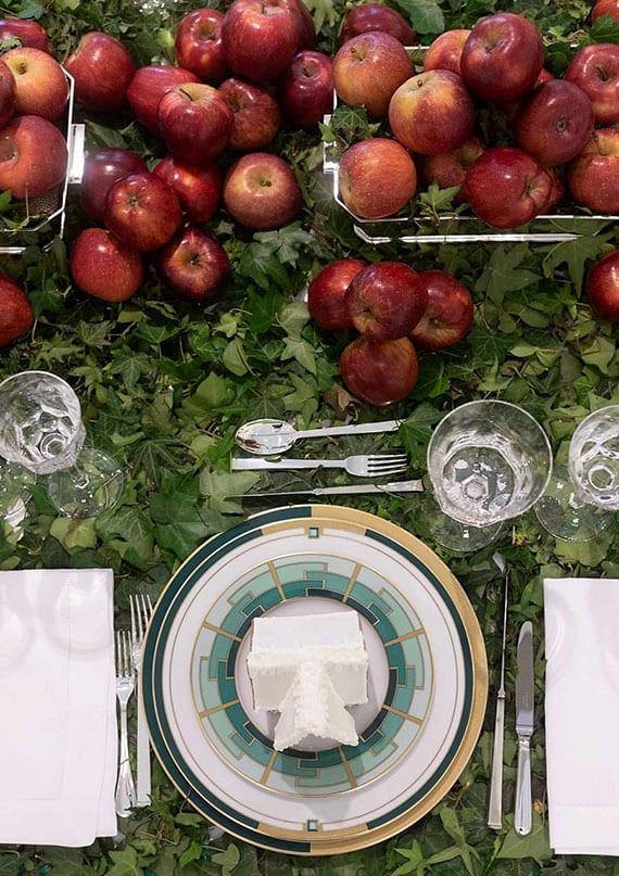 coole tafeldeko herbst mit apfeln als mittelstück, tischdecke aus efeu, silber besteck und eleganten tellern in gold und smaragdgrün