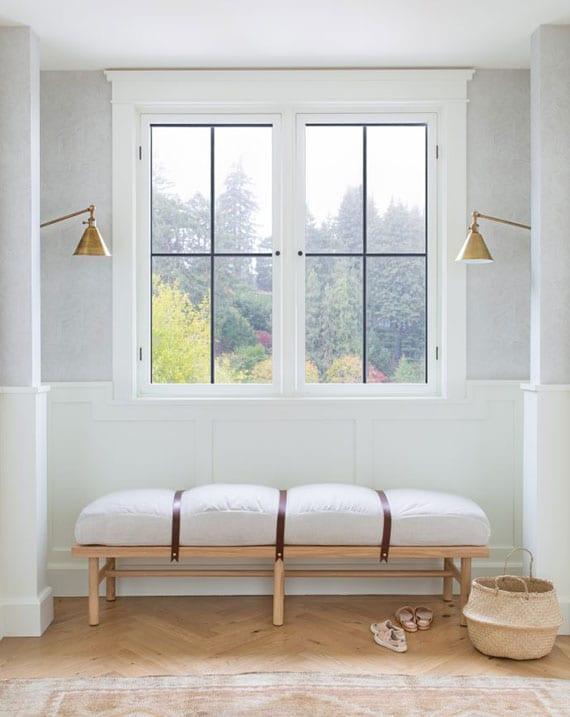 stilvolle und schlichte einrichtungsidee für diele mit designer holzsitzbank mit polster unter fenster, wandleuchten messing und weidenkorb als deko