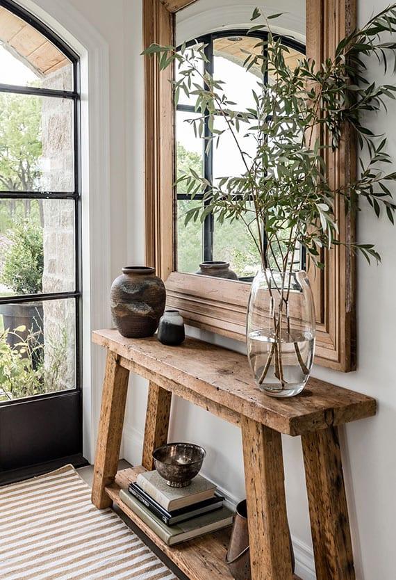 designideen für einladende diele im haus mit schwarzer Sprossentür aus metall, rustikalem konsolentisch holz, deko mit vasen und dielenspiegel im holzrahmen