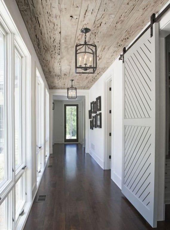 elegantes flur design im rustikalen stil mit dunklem holzboden, holzdeckengestaltung, korridorwand mit fenstern und vintage laterne-lampen