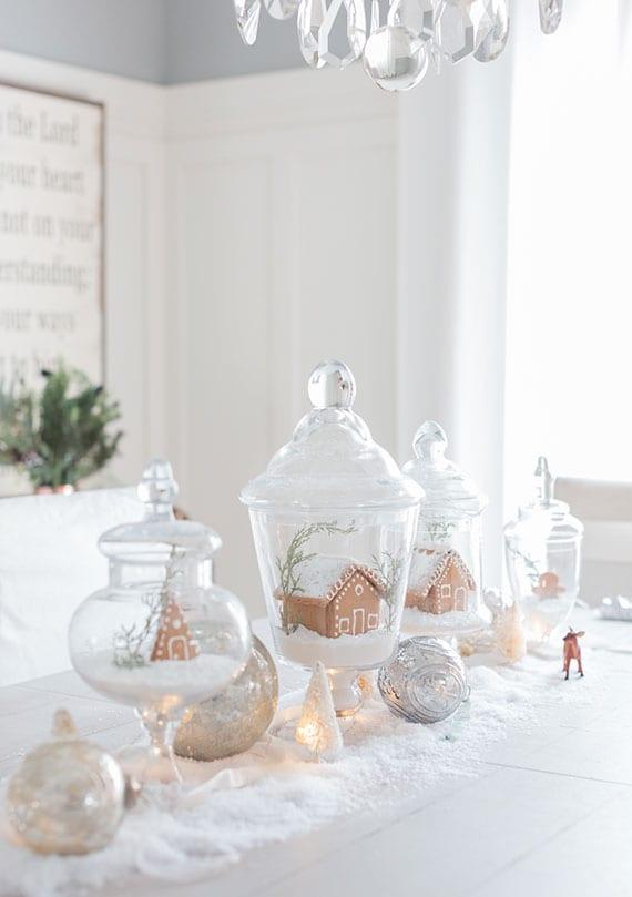 effektvolle weihnachtsdeko idee für Festtafel mit großen und kleinen Lebkuchenhäusern, silber-weihnachtskugeln und kunstschnee